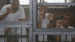 Jazeera journalists (L-R) Mohammed Fahmy, Peter Greste and Baher Mohamed stand behind bars at a court in Cairo May 15, 2014.