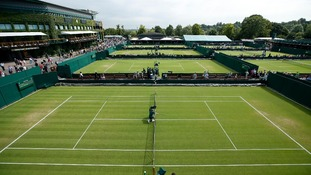 The sky is clear as ground staff prepare the nets for the Wimbledon Championships.