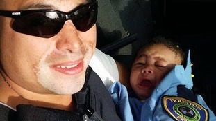 Officer Albert Pizana wrapped Genesis in police uniform upon retrieving her.