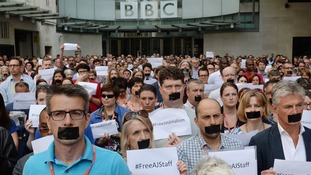 BBC staff in London tape their mouths up in protest at the sentences handed to three Al-Jazeera journalists.