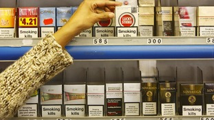 A person grabs cigarettes from a shop shelf.