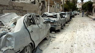 Damaged cars at the site where two bombs detonated near state buildings in Idlib last month