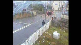 Woman pushes pram past stop sign