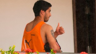 Luis Suarez gives a thumbs up earlier today as he says goodbye to staff and teammates.