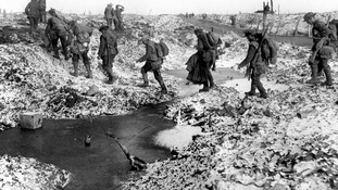 British soldiers negotiating a shell-cratered, Winter landscape along the River Somme in late 1916 after the close of the Allied offensive.
