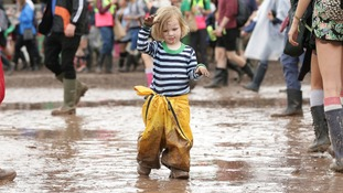 Two-year-old Julia Bristow, from Iowa, USA, walks through a puddle of mud on her first ever Glastonbury visit.