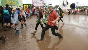 Festival goers manoeuvre through a puddle of mud at the Glastonbury Festival today.