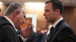 Oscar Pistorius talks to his defence lawyer Barry Roux inside the Pretoria court where his trial is taking place.