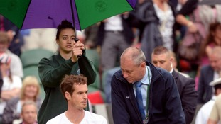 An umbrella is held over Andy Murray after his match against Kevin Anderson is suspended.