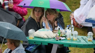 Fans brace the rain to watch Murray at Wimbledon.