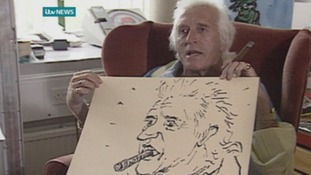 Jimmy Savile poses with the portrait Rolf Harris drew of him.