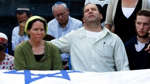 The parents of Naftali Fraenkel,16, mourn beside the coffin of their son.