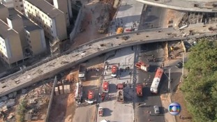 An aerial view of the scene shows the yellow bus wedged under the overpass.