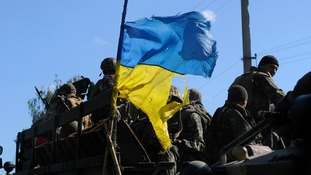 Ukrainian soldiers drive a military vehicle with a torn Ukrainian flag at a checkpoint near Slaviansk.