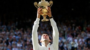 Djokovic holds up the Wimbledon trophy.