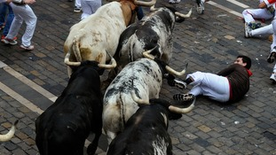 A runner falls in front of the Torrestrella fighting bulls.
