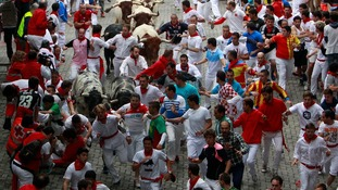Runners dress in white with red neckerchiefs and many spectators stay up drinking all night in bars beforehand.