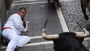 A man watches from the floor as a bull charges towards him.
