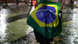 A Brazil fan walks in the rain after watching a broadcast of the World Cup semi-final.