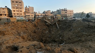 Palestinians stand atop the rubble of a house which police said was destroyed in an Israeli air strike.