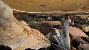 A Palestinian man searches for belongings under the rubble of a house in Gaza City.