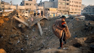 A Palestinian child carries a duvet as he walks past rubble near his home.