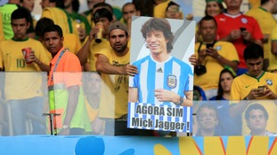 A fan holds a placard with Jagger in an Argentina shirt.