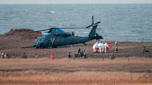 The bodies of the US aircrew are removed from the crash site.