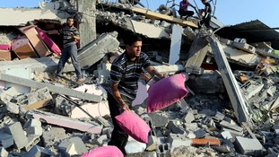 Palestinians collect their belongings from the rubble in Rafah, southern Gaza Strip.