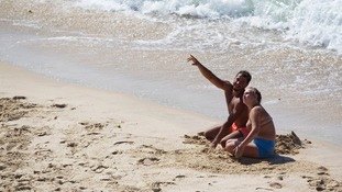 Two Israeli beach-dwellers watch an Iron Dome rocket intercepting a rocket launched from Gaza.