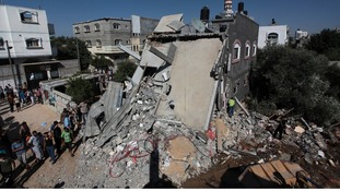Palestinians stand next to a destroyed house following an Israeli air strike in central Gaza Strip today.