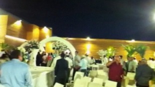 Guests at a wedding in Holon, central Israel, flee as rockets are fired at the venue.