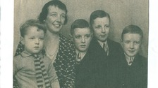 Black and white family photo of nurse Mary Hicks with her four young sons all in shirts and ties