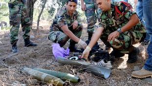 A Lebanese army personnel inspects the remains of a shell in southern Lebanon.