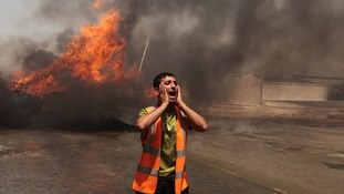 A palestinian man calls for help to put out a fire in Gaza caused by Israeli tank shelling.