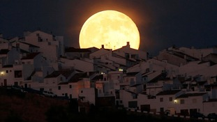 "The ""supermoon"" rises over houses in Olvera, Spain."