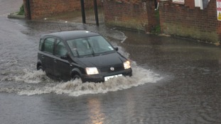 A car struggles through the flood water on Beccles Road in Gorleston, Norfolk.