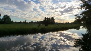 Summer skies reflected in the River Waveney at Bungay in Suffolk.