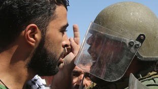 A Palestinian protester argues with an Israeli soldier during a protest against at Hawara checkpoint near the West Bank city of Nablus