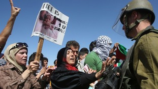 Palestinian protesters argue with Israeli soldiers during a protest against the Israeli air strikes in Gaza strip.