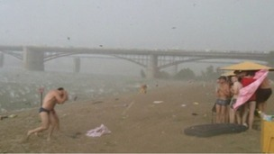 Beachgoers run for cover as a surprise hailstorm strikes in Siberia.