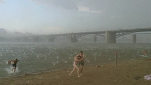 Swimmers dart out of the water and run for cover during a hailstorm in Novosibirsk, Siberia.
