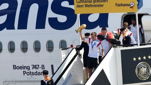 Captain Philipp Lahm holds the trophy aloft as the side leave the plane.