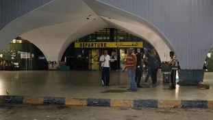 Fighters stand outside the departures terminal at Tripoli's international airport