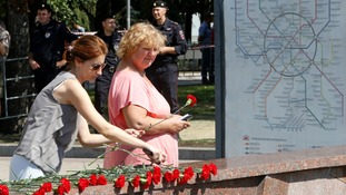 Women lay flowers in memory of victims of Tuesday's crash.