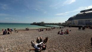 People enjoy the sun on the beach in Worthing in Sussex.