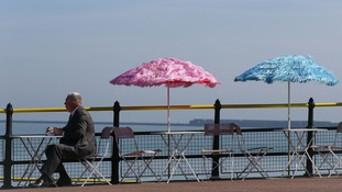 A man enjoys his lunch in the sunshine on the promenade in Dover, Kent.