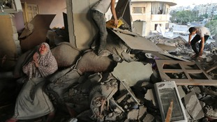 A Palestinian woman cries inside her damaged house in Gaza, targeted overnight in an Israeli airstrike.