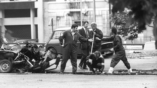 Forensic officers work on the remains of the IRA car which housed the Hyde Park car bomb in which four soldiers died.