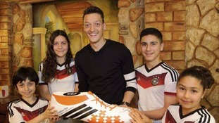 Mesut Ozil and children pose for a BigShoe photo shoot.